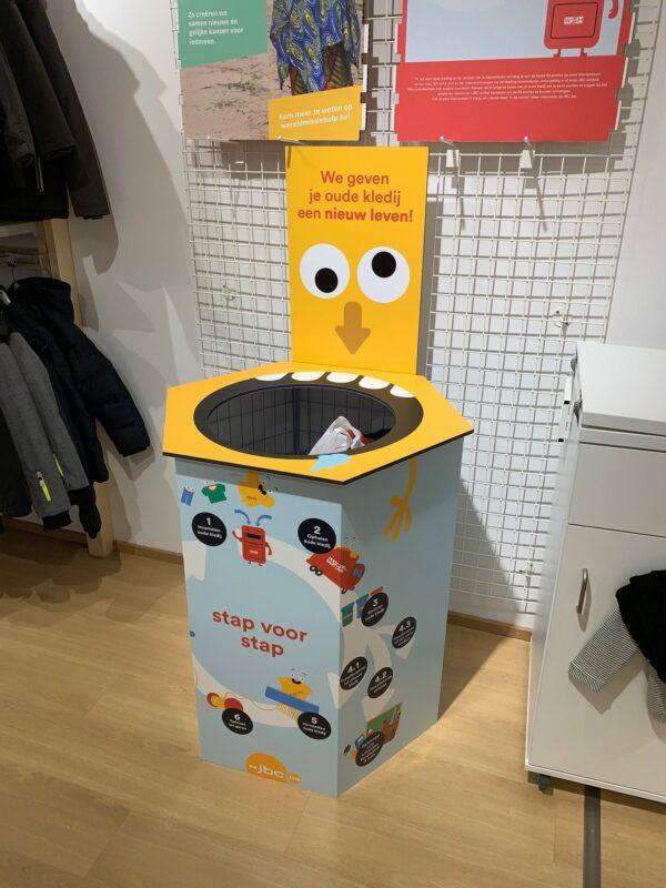 Fun design van actie display uit reboard karton voor het verzamelen oude kledij.