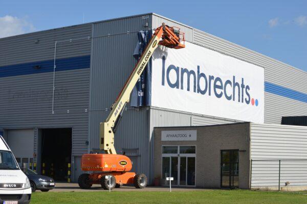 Banner met naam tegen het gebouw van Lambrechts.