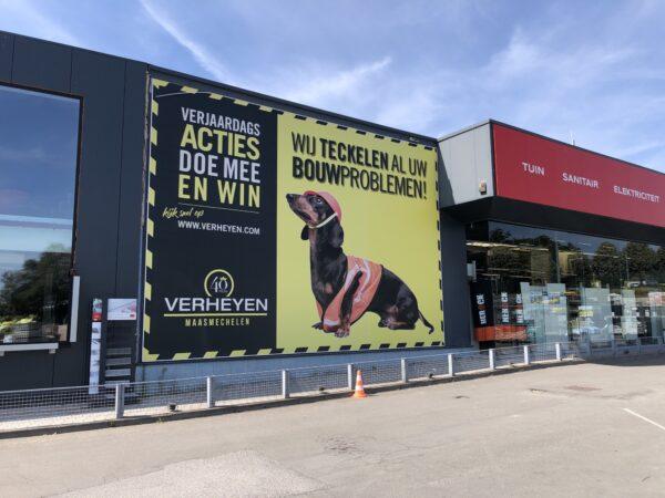 Klopkader reclame acties tegen de muur van het gebouw van Verheyen te Maasmechelen.