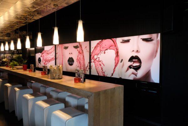 Rechthoekige lichtbak met foto's van gezichten op geplaatst tegen de muur van een tapasbar.