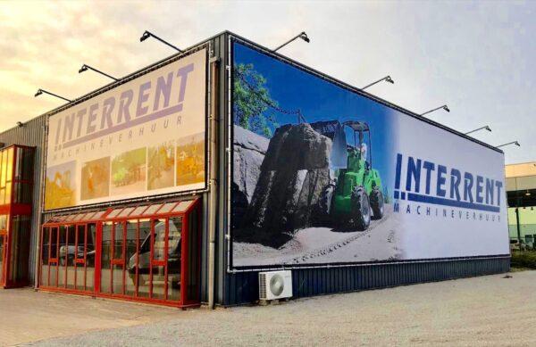 Spandoek banner groot met verlichting tegen de winkel hal van Interrent.