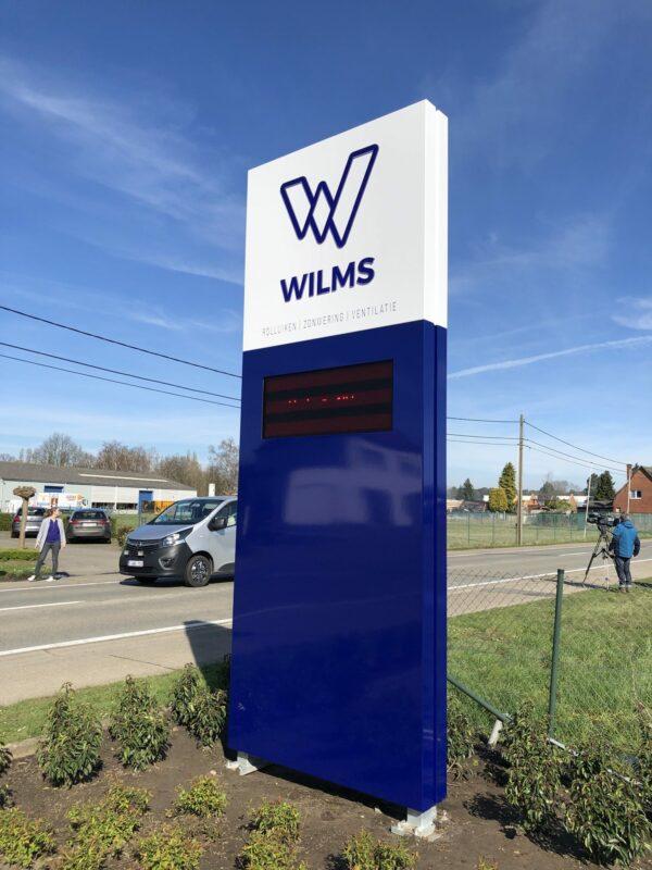 Reclamezuil met logo en naam van Wilms langs de straat.