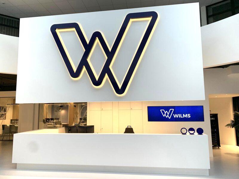 erlicht logo niet verlicht Wilms tegen de wand boven de balie van de showroom van Wilms in Meerhout.