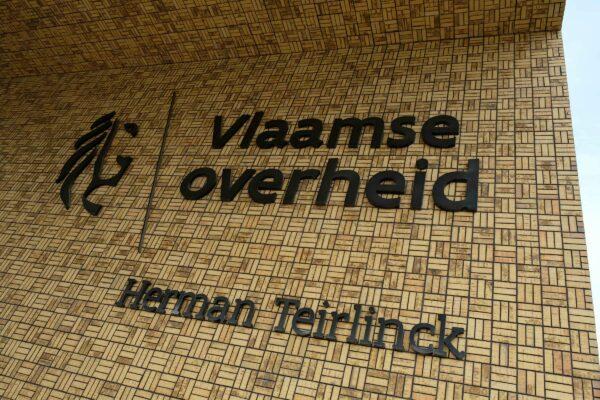 Gevelletters + logo van Vlaamse Overheid tegen gebouw.