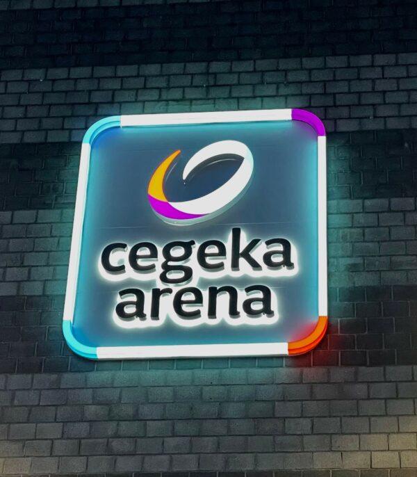 Verlicht logo van Cegeka Arena voor KRC Genk tegen muur voetbalstadion.